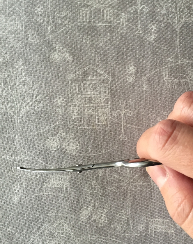Blunt-tip manicuring scissors are thin and bend upward at the end.